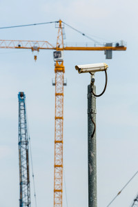 Time-lapse surveillance camera on tower with cranes in the background